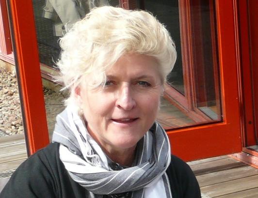 Profilbild av Jill Nyberg. Jill har vitt, kortklippt hår och bär svart blus samt gråvit scarf.