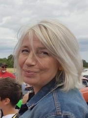 Profilbild på Ann Malmenholt. Ann har vitt, axellångt hår. Hon är utomhus och bär jeansjacka.